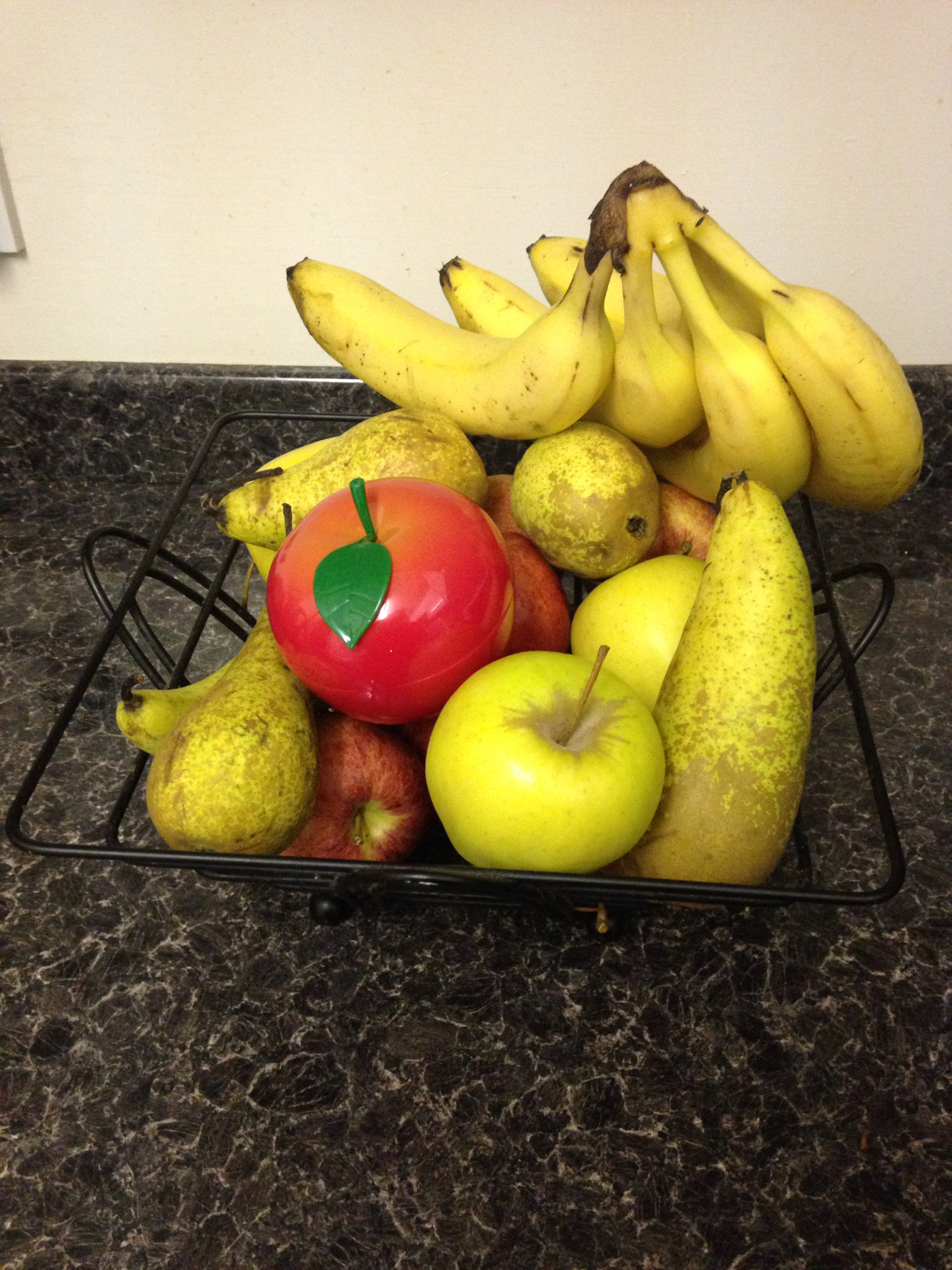A fruit bowl on a black background with apples, pears, bananas, and Tony Moly Appletox